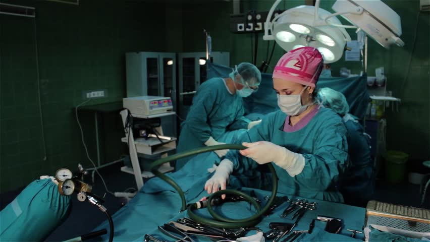 Surgeons team performing operation in hospital operation room,nurse adding surgical tools,needle and spread,surgeon drilling bone,attaching implant,wide angle,holding hand surgical instruments. | Shutterstock HD Video #5578817