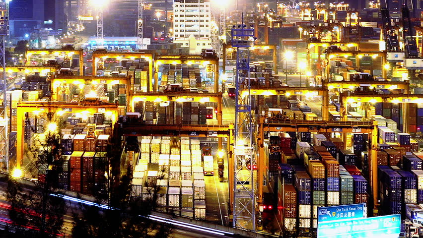 Containers Port Timelapse at Night. Hong Kong. Tight Shot. Cargo containers loading activities in cargo terminal.  Busy traffic across the main road at rush hour. Corporate buildings at the back. #5602319