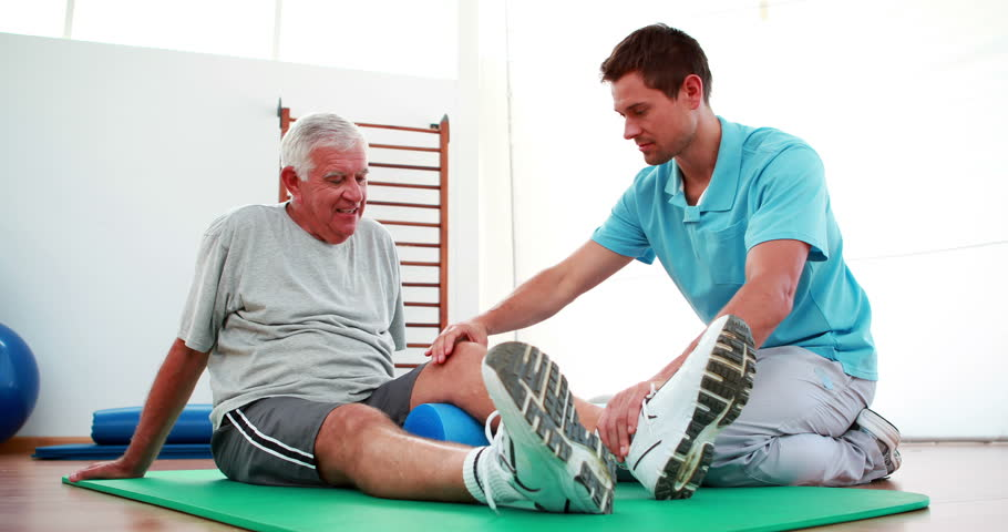 Physiotherapist helping patient with his knee mobility at the rehabilitation center