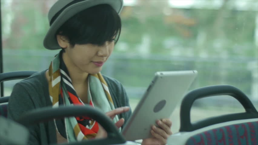 Pretty Young Asian Woman Using A Digital Tablet On A Train