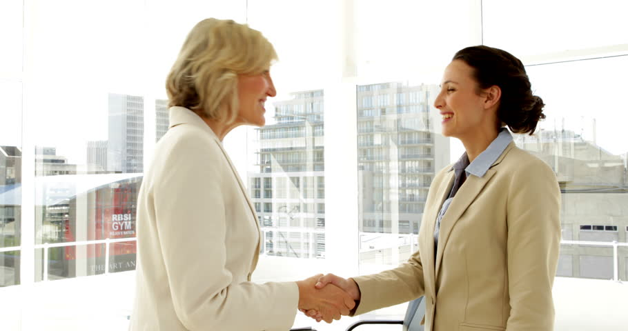 Smiling businesswomen shaking hands in the office | Shutterstock HD Video #5658782