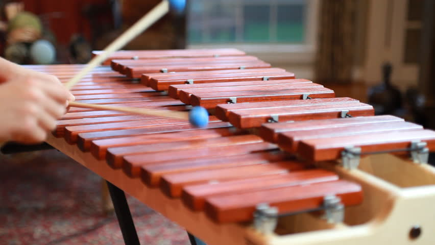 Close up of a boy using blue tipped mallets to play a tune on a marimba.