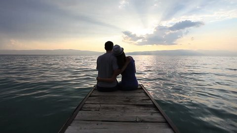 Young heterosexual couple kissing at the beach on sunset
