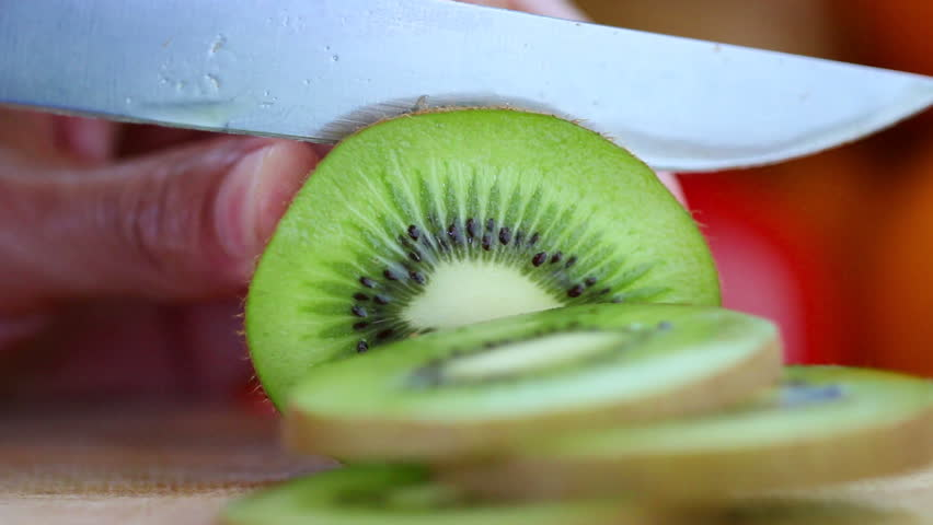 Hand slicing a kiwi  with a knife, close up, HD 1080P