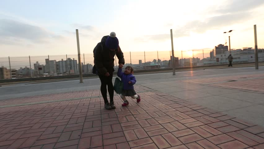 8) Glide cam video shot of an Asian baby and mother playing at a park  during a wintery sunset.
