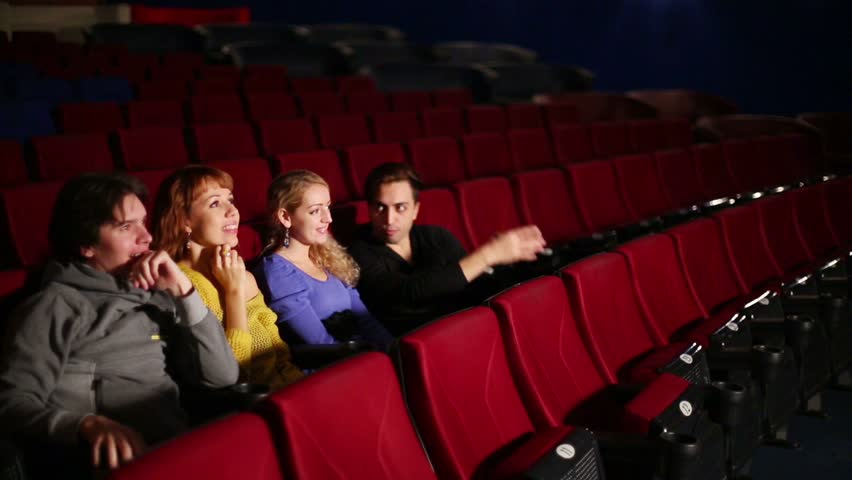 Four people in dark hall cinema watching the film then jump and rejoice