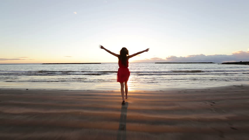 Beach woman running to water in dress at sunset raising arms enjoying freedom during summer holidays vacation travel. Beautiful happy free mixed race Asian Caucasian female girl outside.