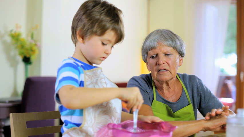 Child teaching how to cook cake to grandmother at home