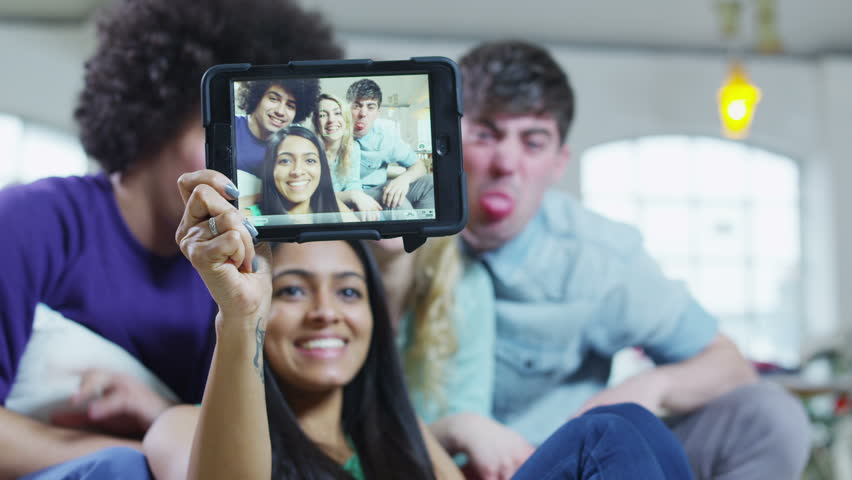 Happy and casual group of young friends at home, posing to take a photograph of themselves with a computer tablet.