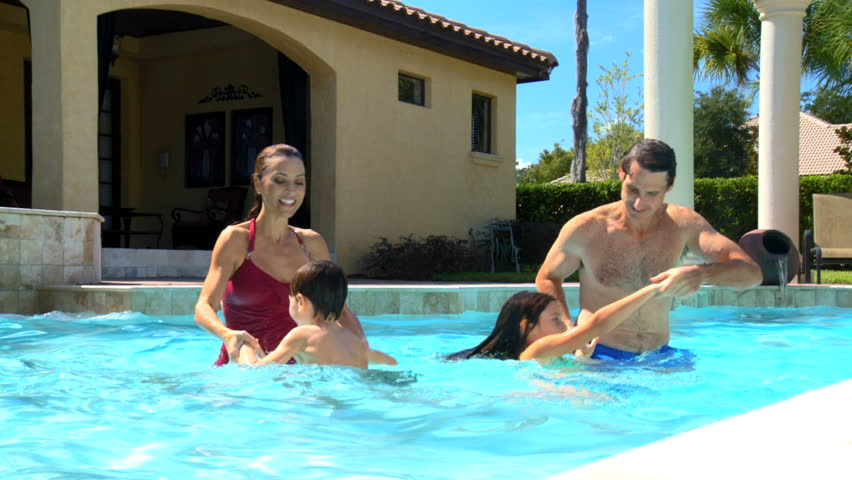 Attractive Young Caucasian Family Enjoying Leisure Time Together In Their Luxury Swimming Pool