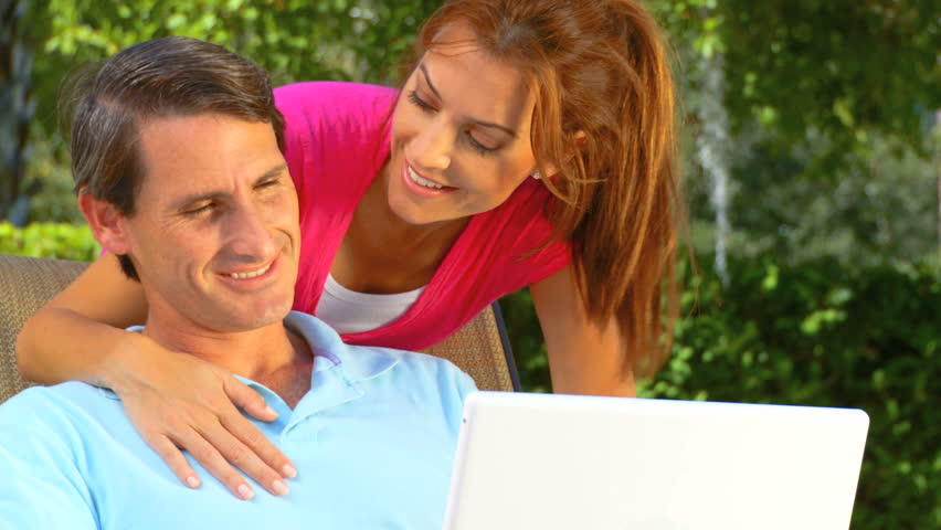 Attractive young heterosexual couple using a laptop outdoors to make future plans