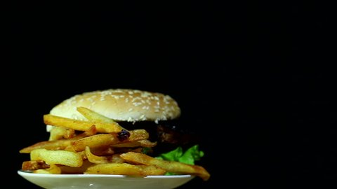 Hamburger with fried potato in rotation on  black background