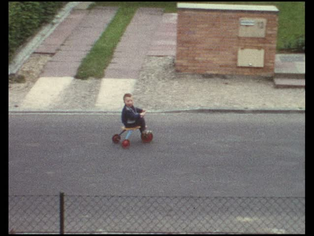 Boy riding trike on street (vintage 8 mm amateur film)