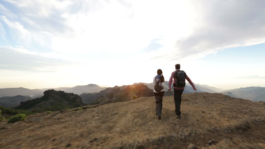 Freedom - Happy couple cheering and running in nature. Hiking man and woman raising arms excited in celebration outdoors. Hikers at sunset in mountain by Roque Nublo, Gran Canaria, Canary Islands | Shutterstock HD Video #5838767
