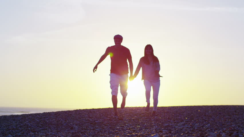 Romantic young couple holding hands and running on the beach as the sun begins to set. In slow motion.