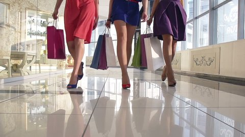 Legs of shopaholics with shopping bags walking down mall