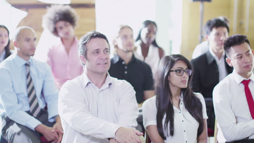 Cheerful diverse business group listening to the speaker at a business presentation or training seminar.  | Shutterstock HD Video #5853317