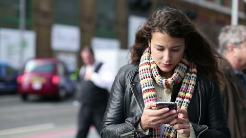 Attractive young woman using a smart phone and looking around whilst out on a public street