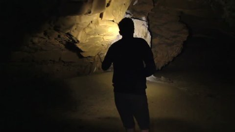 Teenager walking through a giant cave. exploring on journey silhouetted.