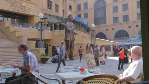 JOHANNESBURG ,SOUTH AFRICA -CIRCA June 2013- a wide shot of people enjoying the patio and people taking pictures of the statue at Mandela square