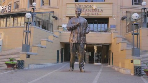 JOHANNESBURG ,SOUTH AFRICA -CIRCA June 2013 - a medium shot of the statue right in front of Nelson Mandela Square with a tourist walking towards it