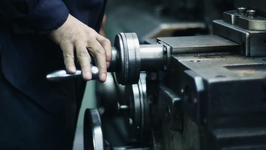 The worker adjusts the machine tool. Rack focus