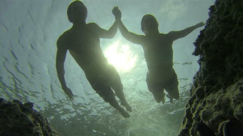 UNDERWATER: Couple swimming holding hands