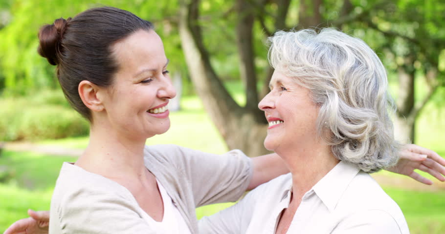 Mother and adult daughter hugging and smiling at camera in the park on a sunny day