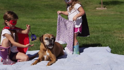 Young girls dressed as superheroes playing outside with their dog - 4K