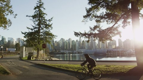 Dolly shot of Vancouver skyline with park, ocean, boats, and cyclist.