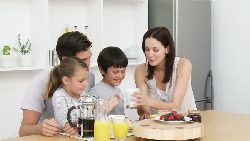 Happy young family having breakfast in the kitchen. Nutritive meal. Footage in high definition