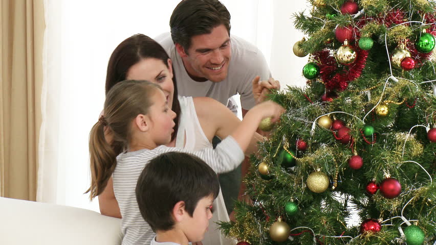 Footage in high definition of family decorating a Christmas tree with balls