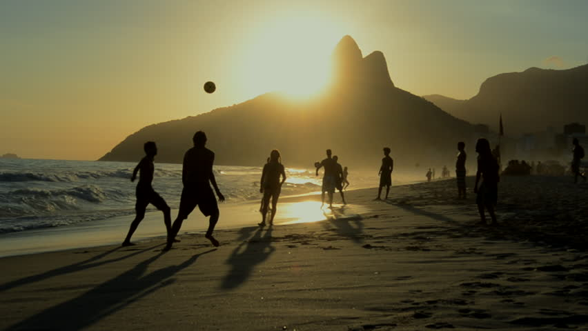 Silhouettes of Carioca Brazilians playing altinho keepy uppy beach football at sunset on Ipanema Beach Rio de Janeiro Brazil | Shutterstock HD Video #5974397