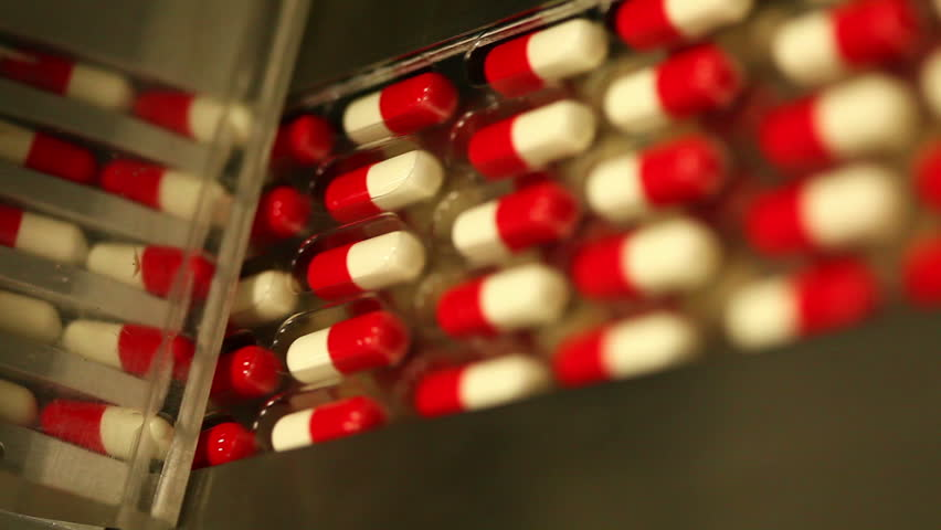 Drug Production. Pharmaceutical machinery for medicine production Pills. Shot ending in a blur defocus scene - ideal to put a text, logo or graphics on it.