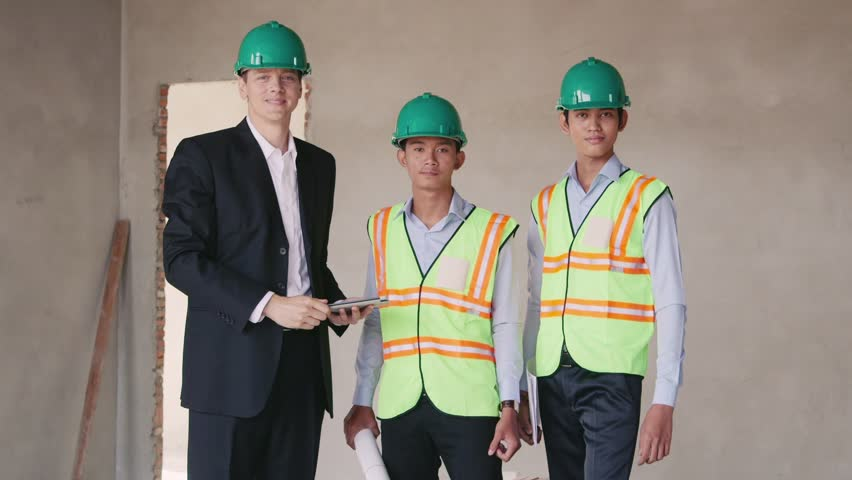 Team at work and collaboration in building industry. Men working in construction site, with architect and asian workers in new apartment reviewing plans and projects on iPad. 6 of 23 | Shutterstock HD Video #5997659