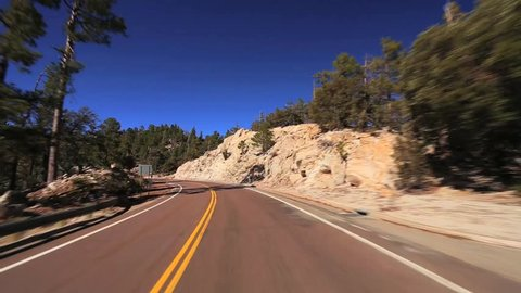Mountain Drive. POV from the drivers perspective through a winding mountain road on a tree lined highway with clear blue skies and burst of sun light.