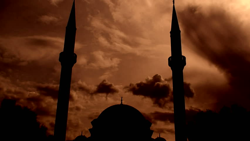 Time lapse clouds flowing past silhouetted twin minaret mosque 4