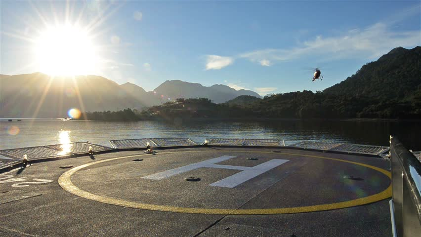Low angle of a helicopter landing on a ship helipad at sunrise near Chait\xED\xA9n in Northern Patagonia in Chile.