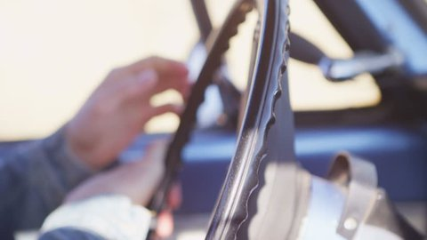 Close-up of hands turning the steering wheel of an old pickup truck.