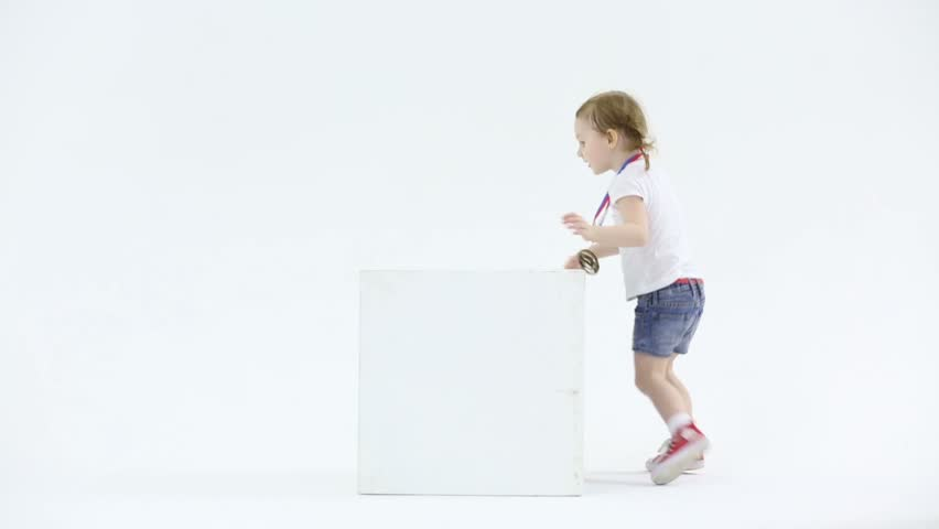 Little girl in shorts with medal on her chest stands on cube and jump down in white studio