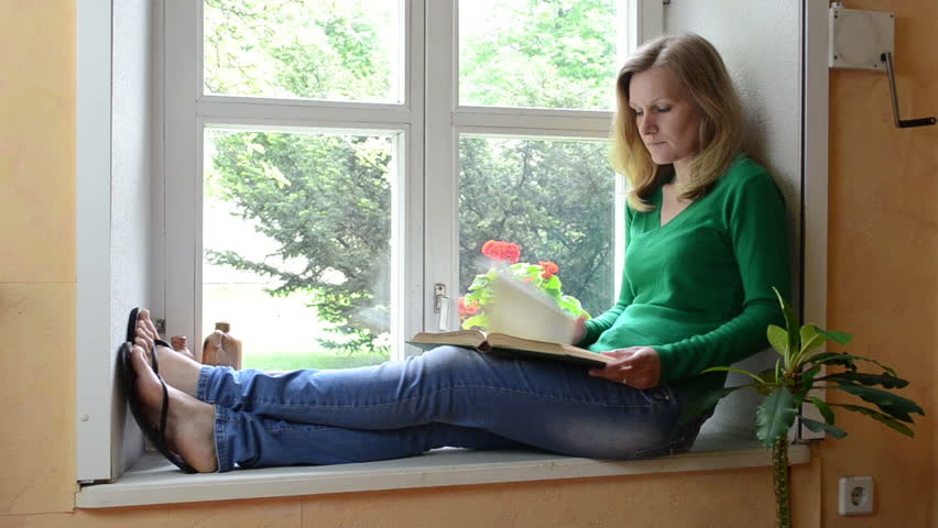 Sit In Window serious face woman sit on windowsill watch through window and read