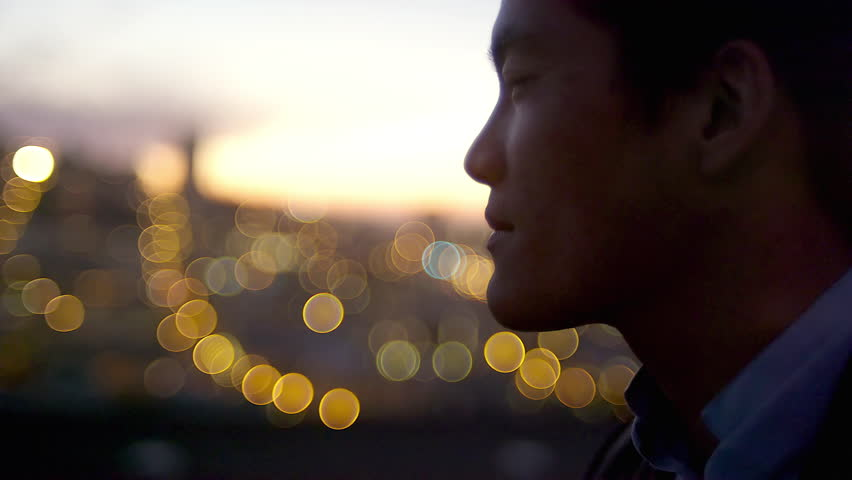 Close up of a man standing on a roof drinking a cocktail at sunset with the city lights behind him