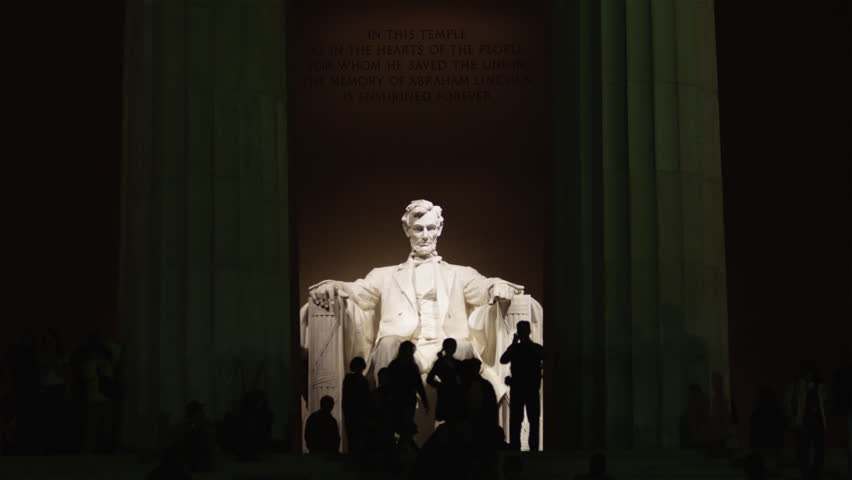 Wide Shot Silhouettes of people in front of Abraham Lincoln statue at Lincoln Memorial illuminated at night, Washington D.C, USA