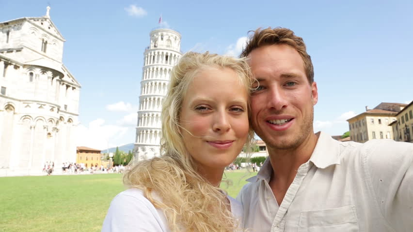 Young couple happy having fun selfie on travel to Pisa. Tourists traveling by The Leaning Tower of Pisa. Beautiful laughing couple in love on romantic holidays vacation. Tower of Pisa, Tuscany, Italy.