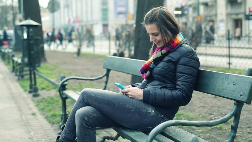 young pretty woman sitting with smartphone in the city park