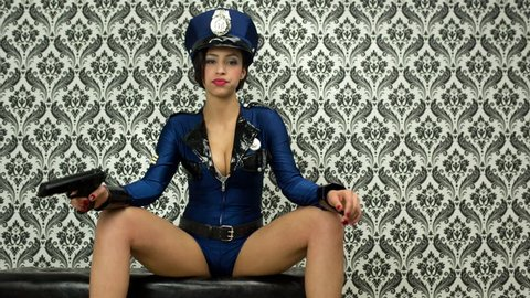 sexy police woman poses against vintage wallpaper with gun. She might arrest you if you're not careful!
