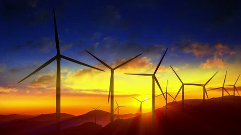 4K Beautiful windmill turbines harnessing clean, green, wind energy silhouetted in the sunrise/sunset sky with sun rays. Green energy. HD Version