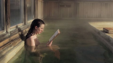 Nude woman reading a book at Japanese Hot springs and spa