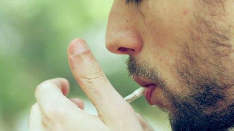 man smoking a joint - close up