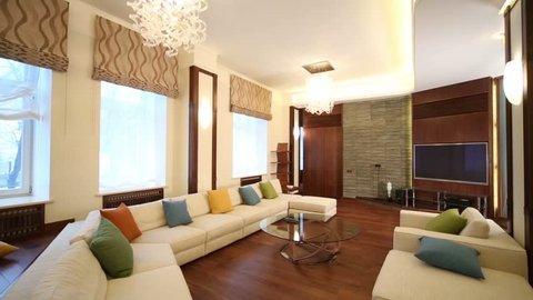 Turning off lights in modern living room with glass table, tv, chairs and sofa